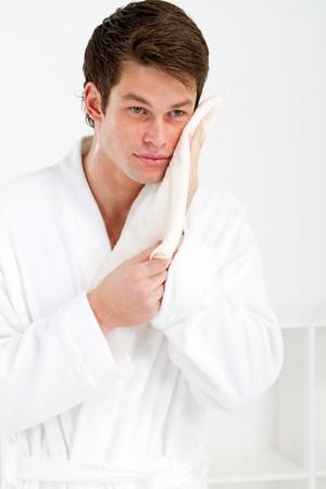 bathrobes: hombre joven lavarse la cara con una toalla