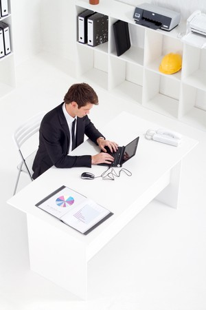 overhead of young businessman working in office photo