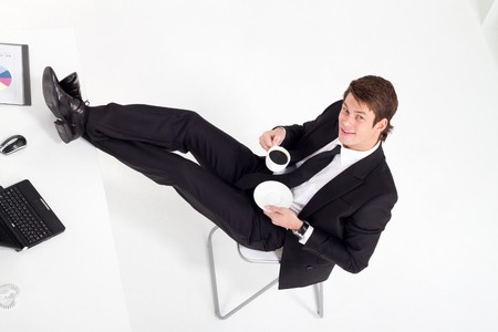 feet on desk: relaxing businessman drinking coffee at desk