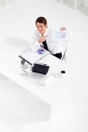happy businessman pointing at sales graph Stock Photo - 7881970