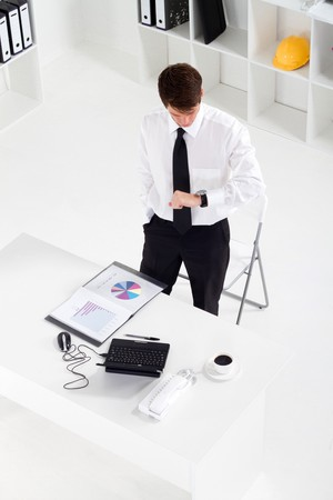 overhead of businessman checking watch in office Stock Photo - 7871577