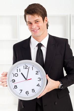 handsome businessman holding a clock photo