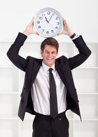 humor young man holding clock on his head photo
