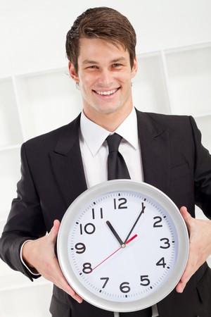 happy businessman holding clock photo