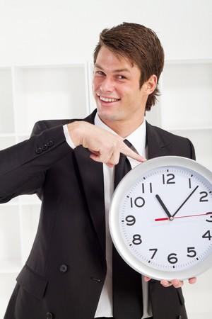 happy buisnessman pointing at clock photo