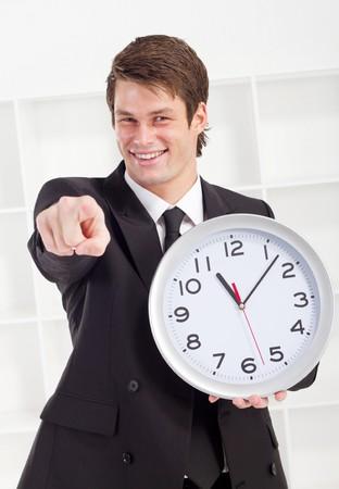 confident businessman holding clock photo