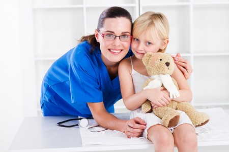 kids hugging: happy nurse and young female patient Stock Photo