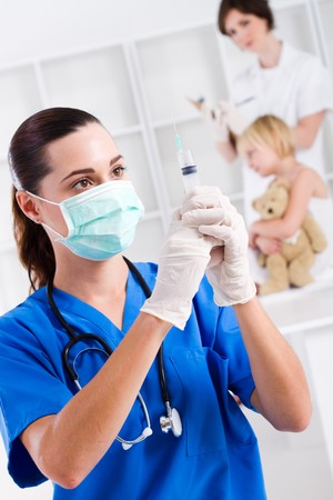gloves nurse: nurse preparing to give little girl injection Stock Photo