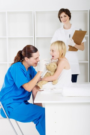 little girl having throat checked by doctor photo