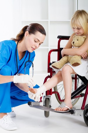 caring nurse bandaging little girls ankle in wheelchair photo