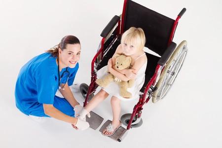 overhead of happy nurse bandaging little girls foot photo