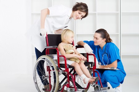caring nurse and doctor chatting to girl in wheelchair photo