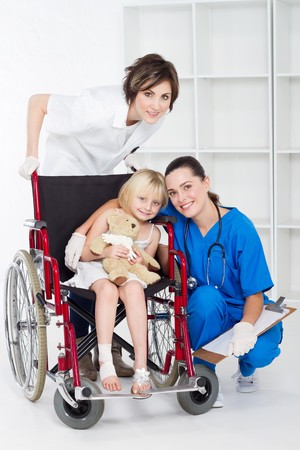 doctor, nurse and little girl patient in wheelchair photo