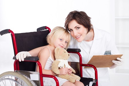 portrait of kind nurse and little patient in wheelchair photo