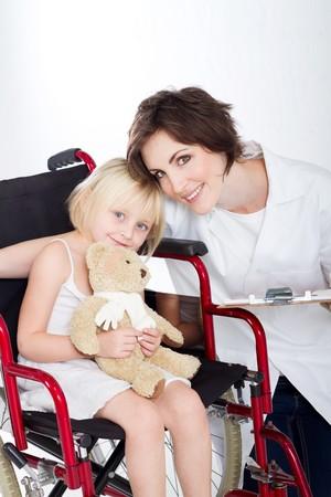 guanti infermiera: premurosa infermiera e sorridente ragazza in sedia a rotelle Archivio Fotografico