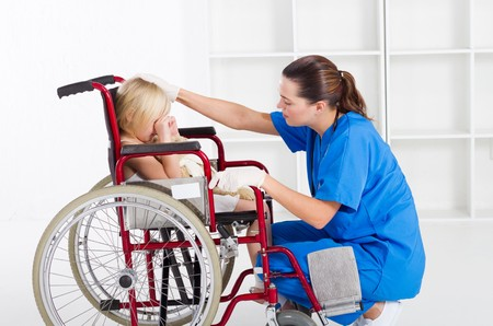 nurse gloves: nurse comforting crying little girl in wheelchair Stock Photo