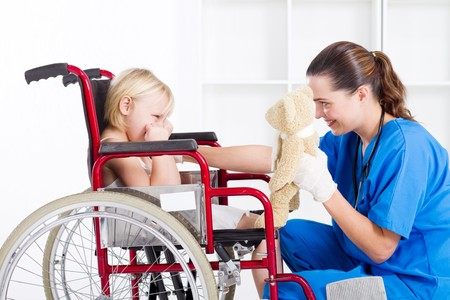 pediatric: nurse cheering up little girl in wheelchair Stock Photo