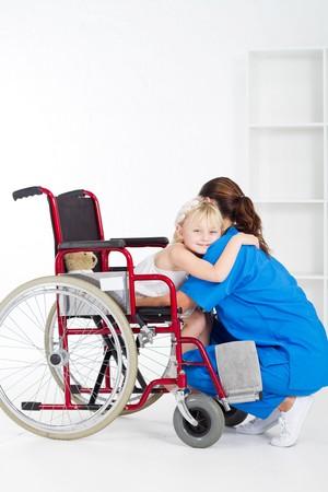 little wheelchair patient hugging doctor photo