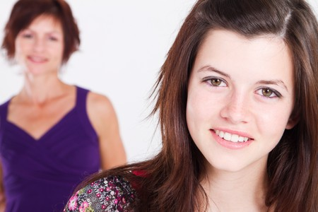 mid teens: happy teen girl with mom in background Stock Photo