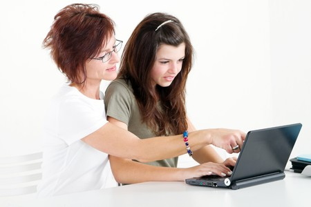 mother helping teen daughter with homework on laptop Stock Photo - 7940079