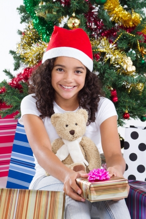 innocent: happy teen girl under christmas tree with gifts
