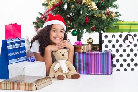 sweet young teen girl posing under christmas tree photo
