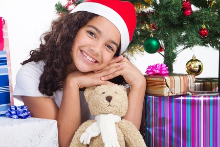 innocent: cute young preteen girl under christmas tree with teddybear Stock Photo