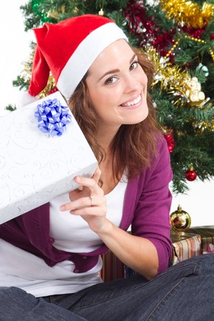pretty christmas woman holding gift under tree photo