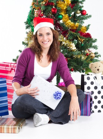 spunky: pretty young woman holding gift under christmas tree
