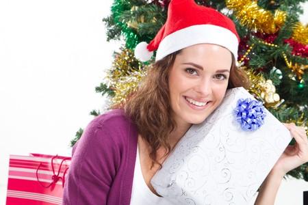 spunky: beautiful woman holding christmas gift under tree