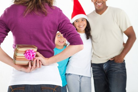 mother surprising happy family with christmas gift photo