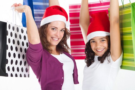 excited mother and daughter with christmas hats and gifts photo