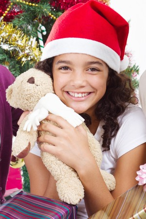 happy pre-teen girl hugging teddy bear under christmas tree photo