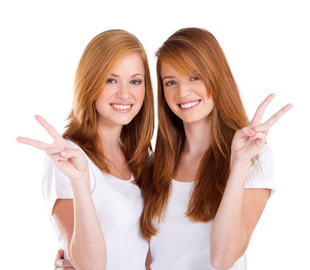 peace sign: happy young sisters giving peace sign