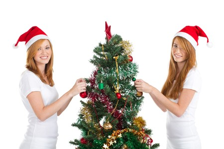 pretty twin girls trimming christmas tree photo