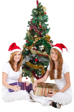 pretty sisters holding gifts under christmas tree photo