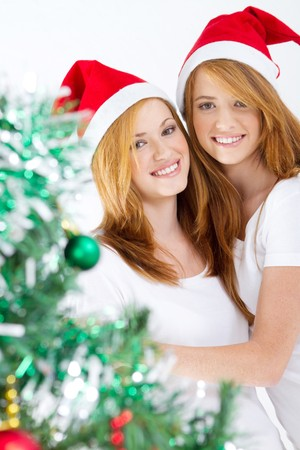 beautiful young sisters wearing christmas hats photo