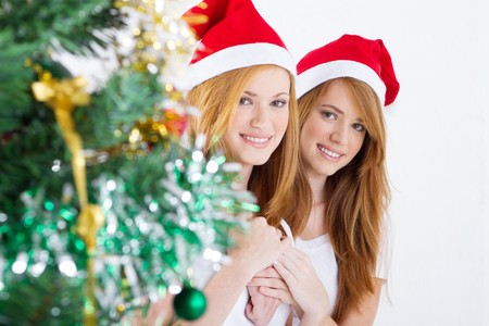 pretty twin sisters next to christmas tree photo