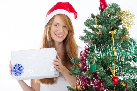 pretty young woman with christmas gift next to tree photo