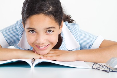 an elementary: pretty young student relaxing at school desk Stock Photo
