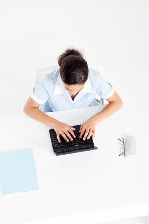 spunky: overhead of school girl using laptop at desk