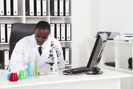 biology lab: african scientist working lab at desk