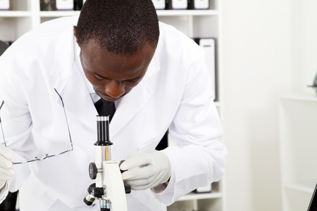 african scientist examining specimens through microscope Stock Photo - 8306651