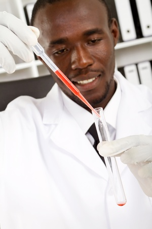medical testing: african scientist conducting experiment in test tube