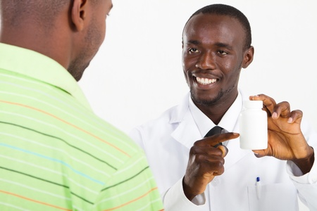 happy african pharmacist prescribing medicine photo