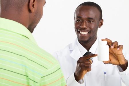 happy african pharmacist prescribing medicine