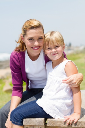 mother on bench: happy mom and daughter outdoors