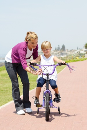 mother teaching daughter to ride bicycle Stock Photo - 8989644