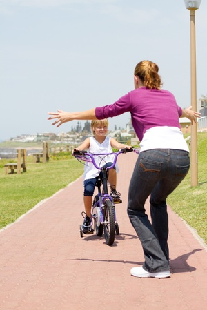 young mom watching daughter ride bicycle photo