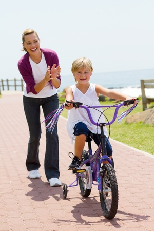 happy mom teaching daughter to ride bike photo